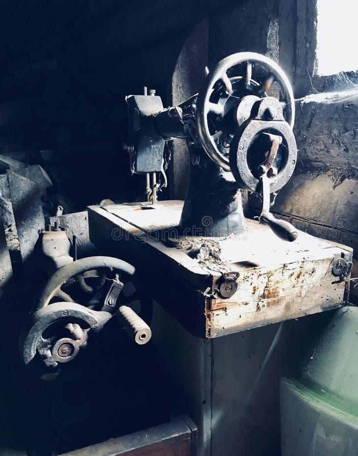 Конец-вверх швейной машины ручного привода старый Покрытый с корозией, пылью и паутинами На фоне деревянного покинутого бара стоковые фотографии rf