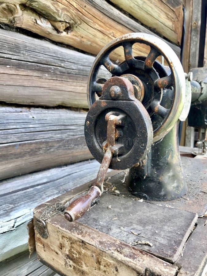 Конец-вверх швейной машины ручного привода старый Покрытый с корозией, пылью и паутинами На фоне деревянного покинутого бара стоковое фото