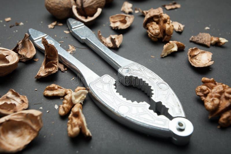 Конец-вверх Щелкунчика и грецких орехов металла на черной предпосылке стоковые фотографии rf