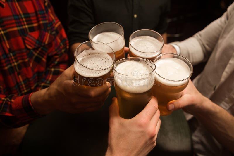 Конец-вверх людей провозглашать с пивом стоковые фото