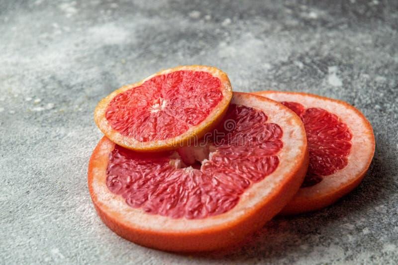 конец вверх Яркие красные кружки отрезанного грейпфрута на серой конкретной предпосылке скопируйте космос стоковые изображения rf