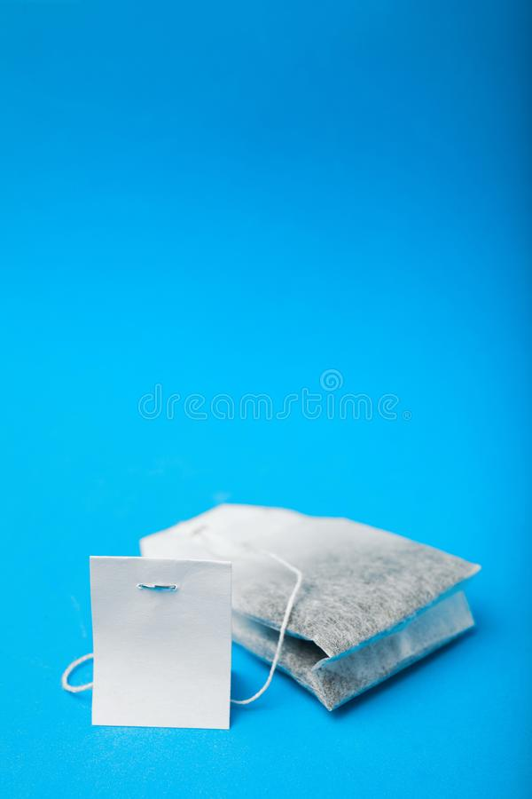 Конец-вверх, ярлык и пакетик чая на голубой предпосылке, вертикальной : стоковое изображение rf
