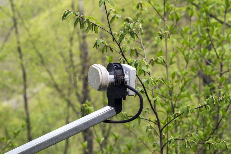 Конец-вверх LNB установил на спутниковой антенне установленной на дом LNB использовано для того чтобы усилить полученный сигнал стоковое изображение