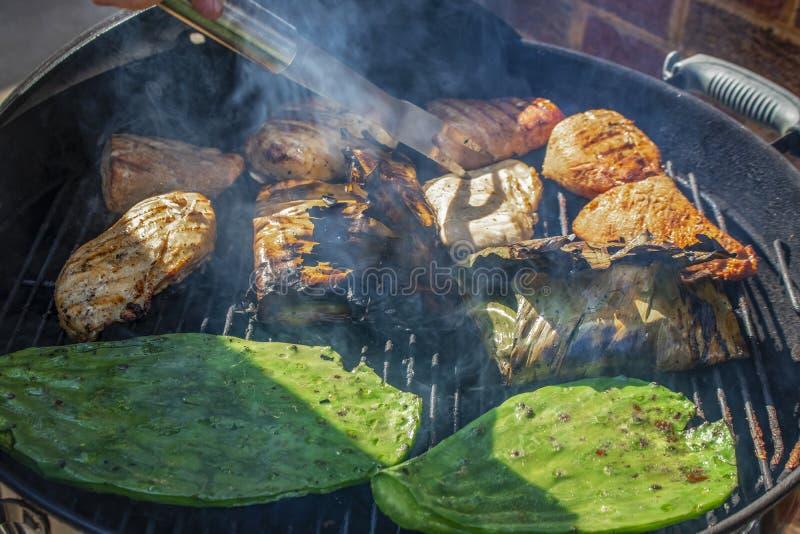 Конец-вверх nopales кактуса и банана листает обернутые рыбы и цыпленок и свинина на гриле угля с дымом и вилка вставленная внутри стоковое фото