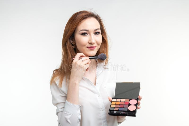 Конец визажиста красоты вверх по корейской красивой молодой женщине довольно усмехаясь держащ щетку палитры тени глаза на белизне стоковые фото