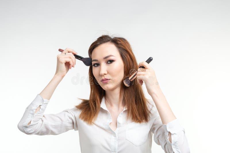 Конец визажиста красоты вверх по корейской красивой молодой женщине довольно усмехаясь держащ щетки макияжа на белой предпосылке стоковая фотография