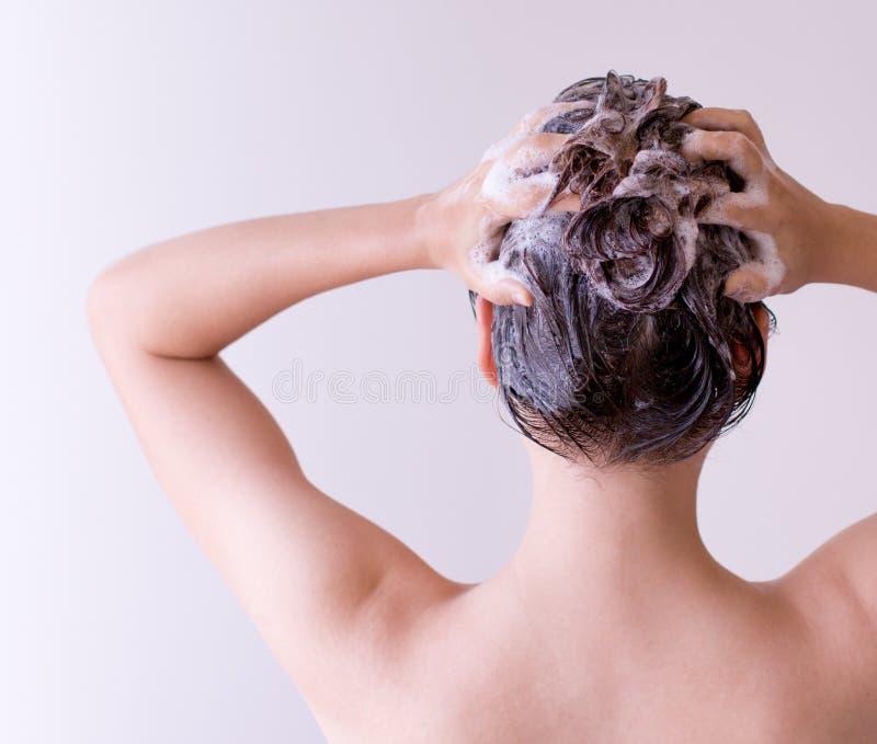 Конец волос шампуней женщины вверх с обеими руками на белой предпосылке стоковая фотография