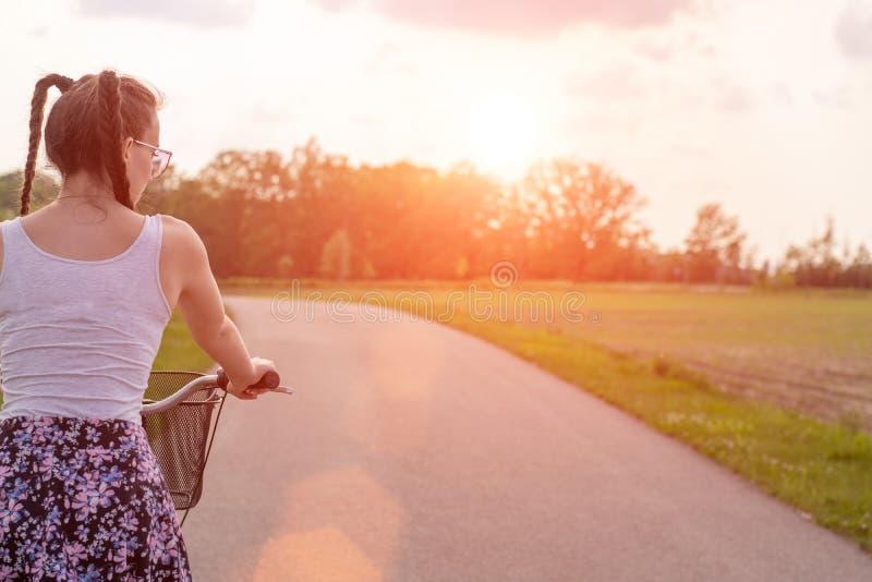 Конец девушки вверх с велосипедом на заходе солнца лета на дороге в парке города Задействовать вниз по улице, который нужно работ стоковое изображение rf