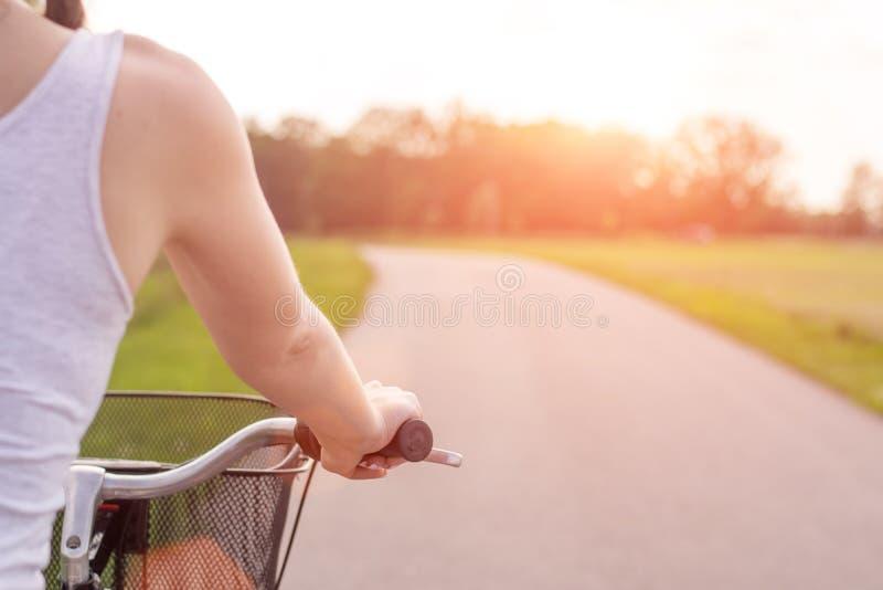Конец девушки вверх с велосипедом на заходе солнца лета на дороге в парке города Задействовать вниз по улице, который нужно работ стоковые фото