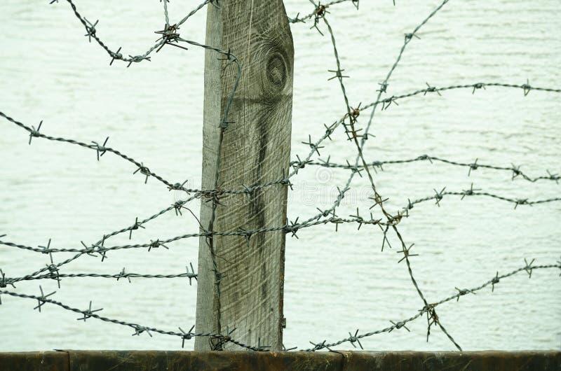 Конец загородки колючей проволоки вверх в военной зоне для того чтобы защитить пленников от избегать лагерь стоковое изображение