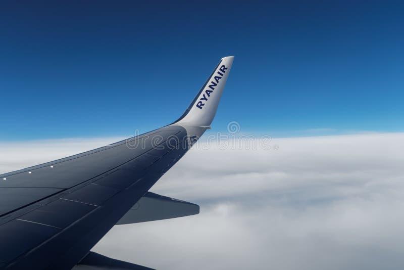 Конец крыла Ryanair на воздушных судн над облаками стоковая фотография rf