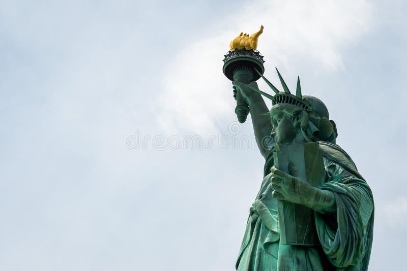 Конец статуи свободы вверх в солнечном дне, голубом небе в Нью-Йорке - изображении стоковые изображения