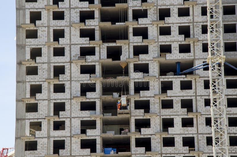 Конец строительной площадки вверх На средних полах, работники разгружают строительные материалы стоковые фото