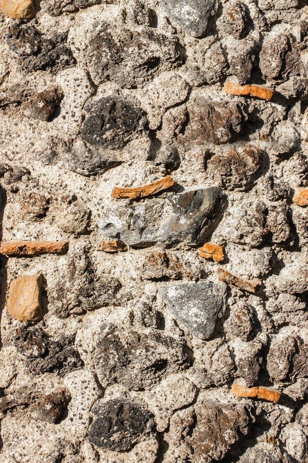 Конец текстуры стены каменного masonry вверх с черным камнем лавы стоковая фотография rf