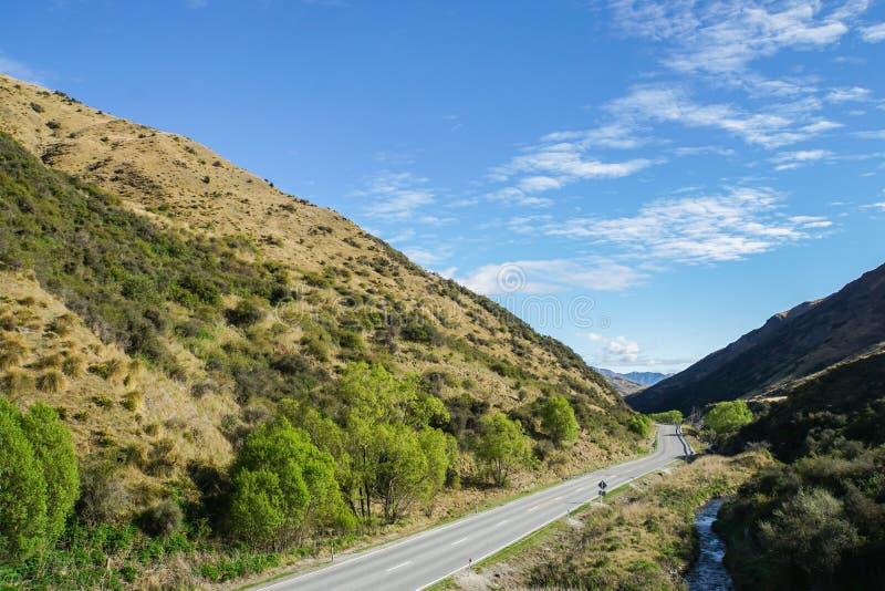 конкретная дорога вдоль зеленых холмов в Новой Зеландии для отключения стоковое изображение