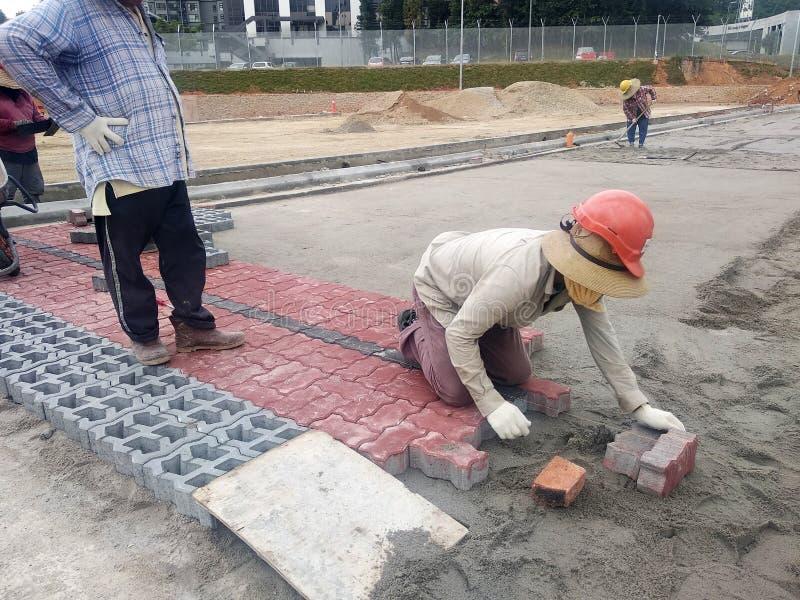Конкретные pavers подготовка и работа установки работниками на районе автостоянки строительной площадки стоковое изображение rf