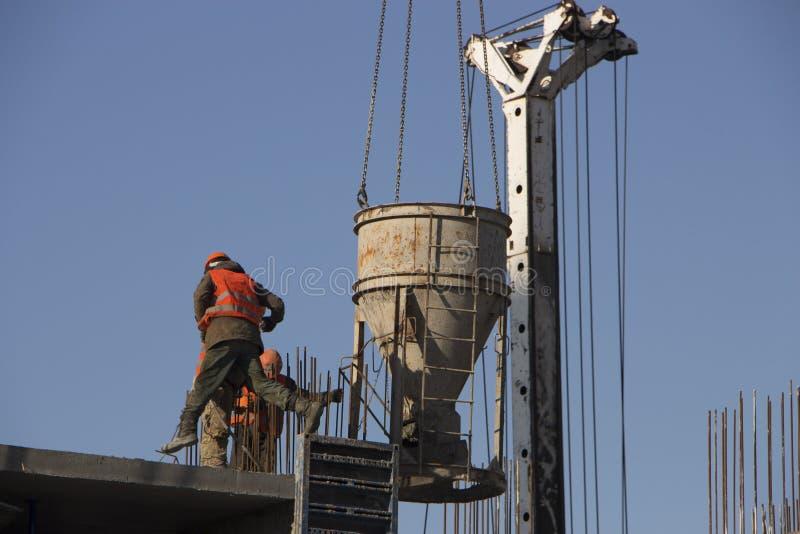 Конкретный лить во время коммерчески concreting полов здания в строительной площадке и гражданском инженере стоковое изображение