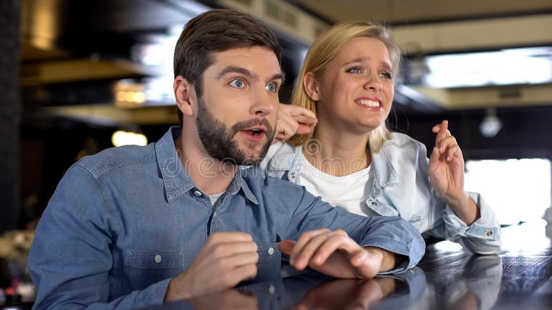 Конкуренция нервных пар наблюдая в баре, поддерживая их фаворитов, потеха стоковые фотографии rf