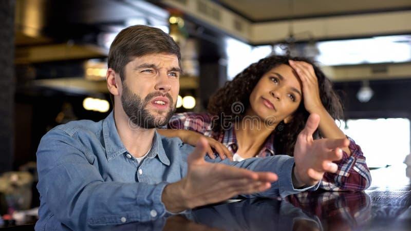 конкуренция спорта Мульти-этнических пар наблюдая, выглядя расстроенный, разочарование стоковая фотография