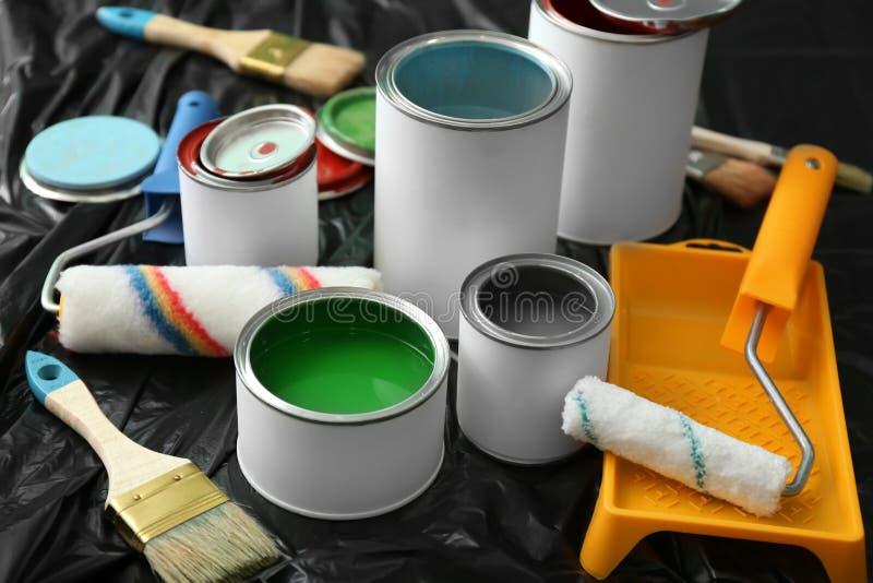 Консервные банки краски, ролика и щетки на пластиковой крышке стоковые фотографии rf