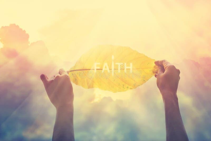 Конспект, держа желтые лист в красочном небе веры, винтажный тон цвета стоковые изображения
