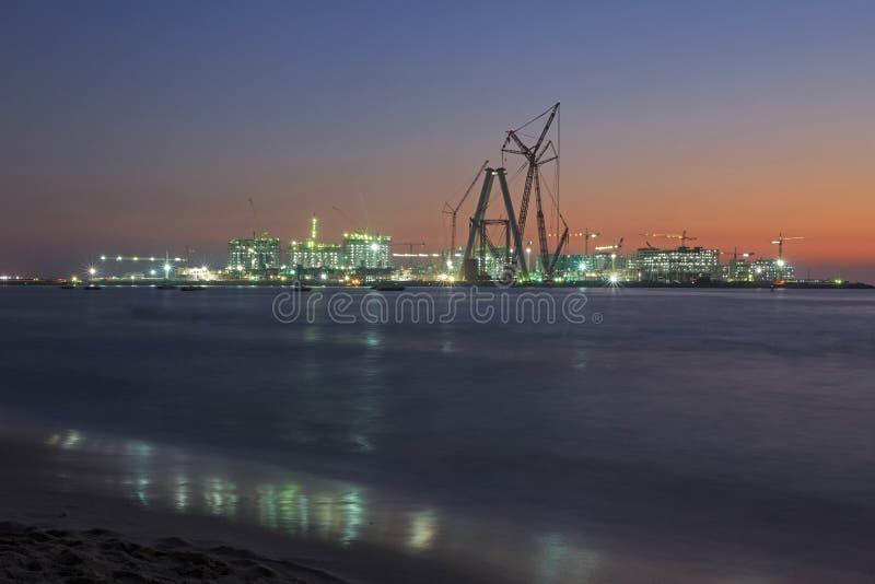 Конструкция в Дубай на ноче стоковое изображение
