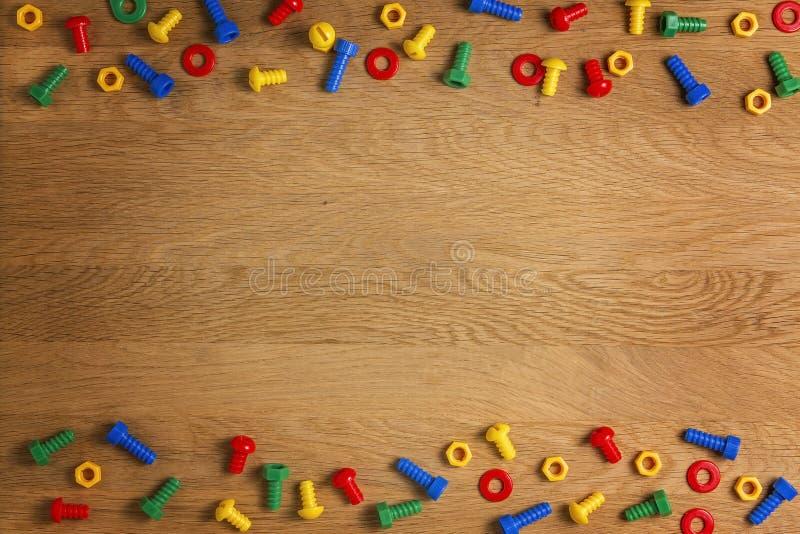 Конструкция детей забавляется винты и гайки на деревянной предпосылке Взгляд сверху Плоское положение Скопируйте космос для текст стоковая фотография rf