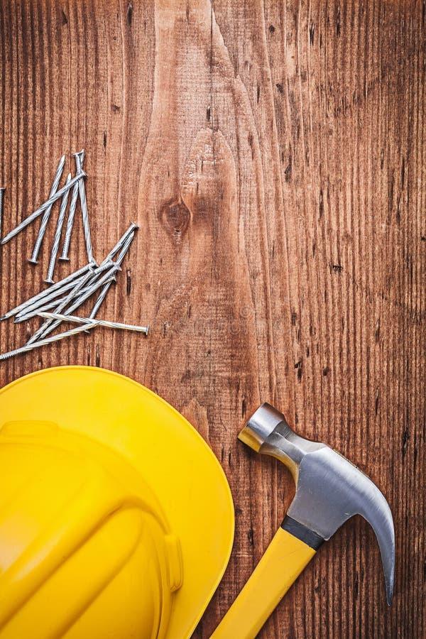 Конструкция металла молотка с раздвоенным хвостом пригвождает трудную шляпу на деревянной доске стоковые изображения rf