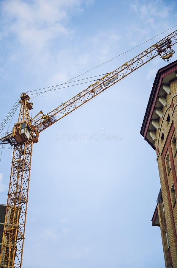 Конструкция многоквартирного дома Кран с поднимающейся укосиной против неба, взгляд снизу стоковые фото