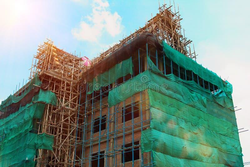 Конструкция с районом места деятельности, леса с строительной конструкцией и работник в дневном свете стоковое изображение