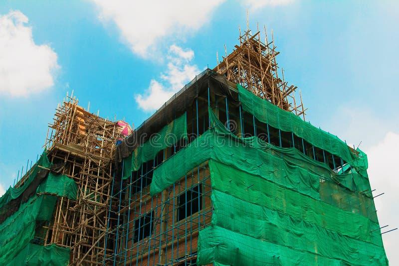 Конструкция с районом места деятельности, леса с строительной конструкцией и работник в дневном свете стоковая фотография rf