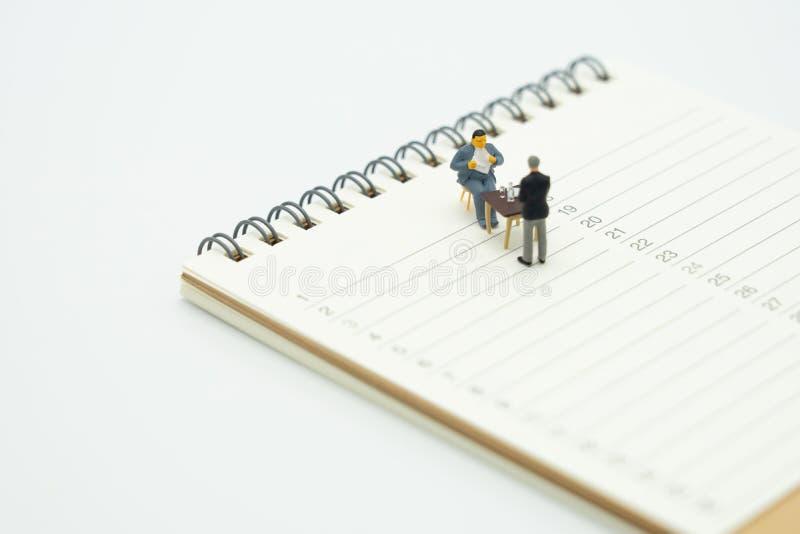 Консультационные услуги миниатюрных людей сидя советуя со для того чтобы оплатить коммерческие деятельности налогов на встрече сп стоковые фото