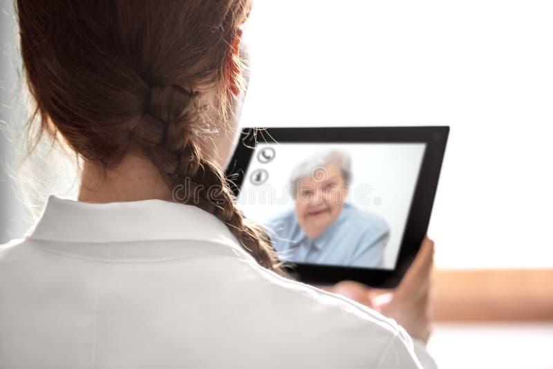 Консультация Doctorс телемедициной или telehealth, пожилыми стоковое фото rf