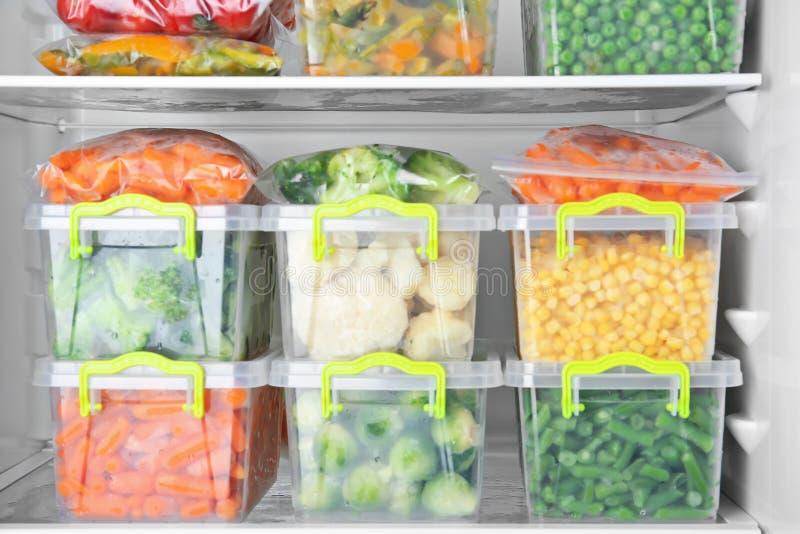 Контейнеры с глубоко -, который замерли овощами стоковые фотографии rf