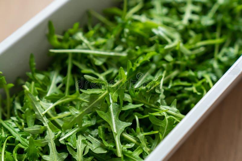 Контейнер свежего зеленого, естественного arugula на деревянной предпосылке стоковые фотографии rf