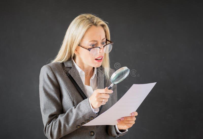 Контракт дела чтения женщины с лупой стоковое изображение rf