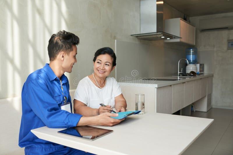 Контракт ремонтника и домохозяйки подписывая стоковые фото