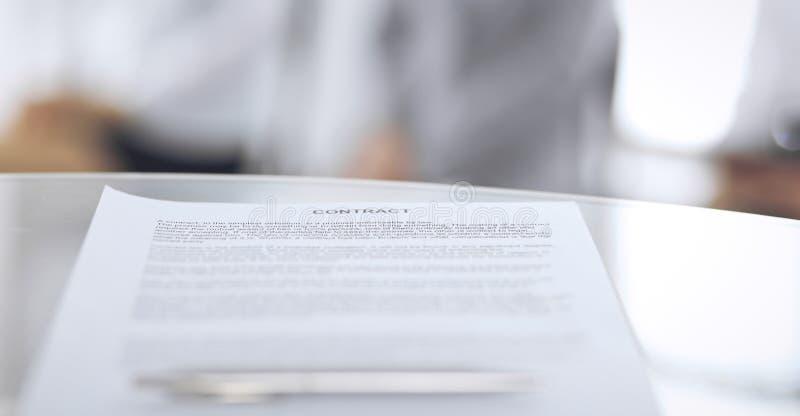 Контракт с ручкой и запачканными бизнесменами на предпосылке, концом-вверх Женские выбранные ждать интервью на стоковое фото
