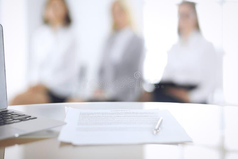 Контракт с ручкой и запачканными бизнесменами на предпосылке, концом-вверх Женские выбранные ждать интервью на стоковое фото rf