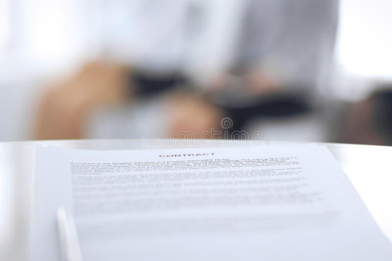 Контракт с ручкой и запачканными бизнесменами на предпосылке, концом-вверх Женские выбранные ждать интервью на стоковое изображение
