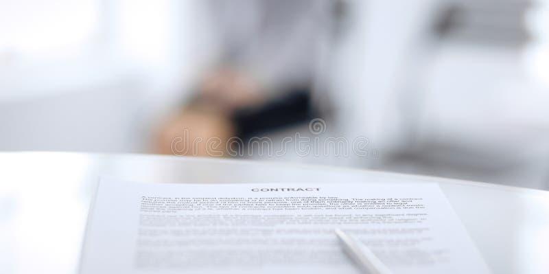 Контракт с ручкой и запачканными бизнесменами на предпосылке, концом-вверх стоковое фото