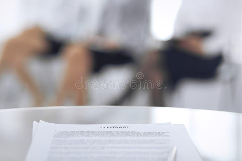 Контракт с ручкой и запачканными бизнесменами на предпосылке, концом-вверх Женские выбранные ждать интервью на стоковые изображения