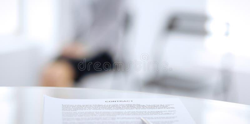 Контракт с ручкой и запачканными бизнесменами на предпосылке, концом-вверх стоковое фото rf
