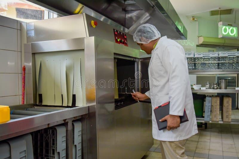 Контролер еды человека в равномерных проверках кухня ресторана стоковые изображения