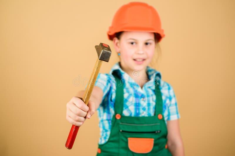 Контролер мастера Маленькая девочка в шлеме с молотком Работник ребенк в трудной шляпе День Труда 1 может ремонтная мастерская бе стоковая фотография rf