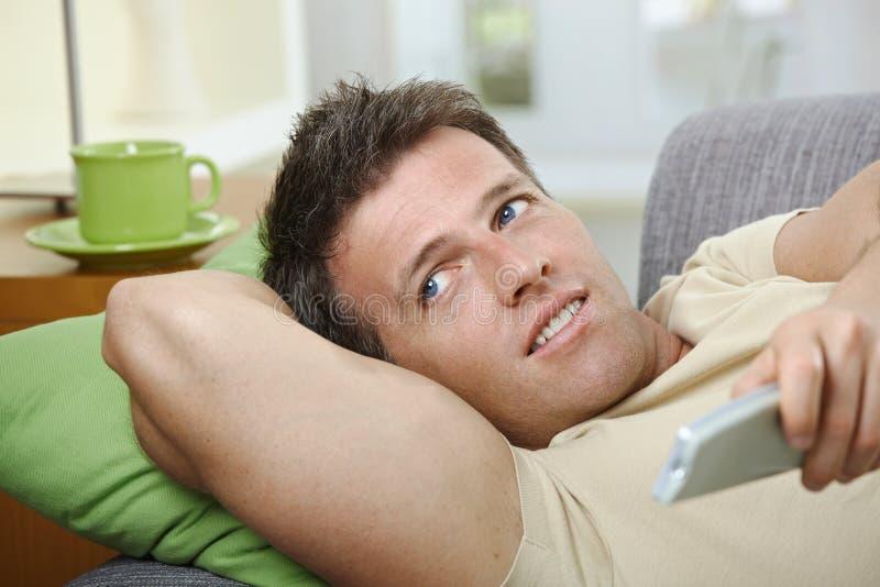 контролируйте софу человека дистанционную сь используя стоковые изображения rf