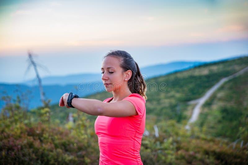 Контрольное время женщины на ее вахте спорта во время хода следа стоковое фото rf