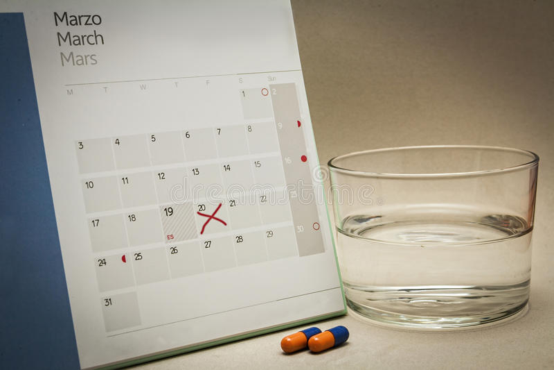Контролируйте пилюльки на календаре стоковые фото