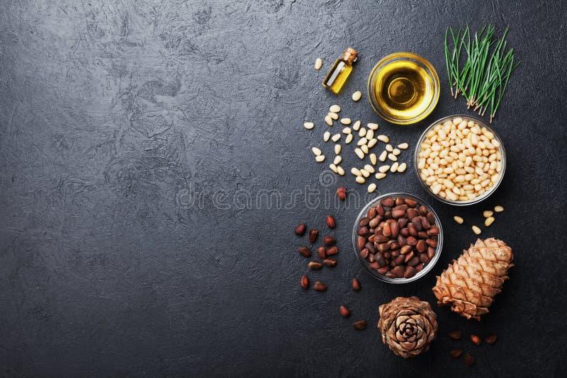 Конусы гаек сосны, масла и кедра на черном взгляде столешницы Органическое и здоровое superfood Скопируйте космос для текста Плос стоковое фото