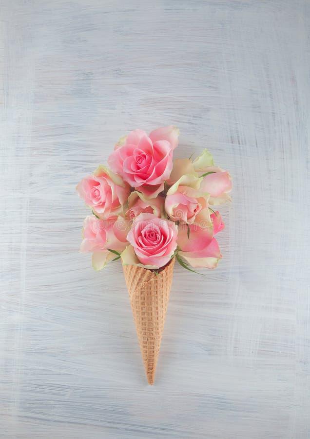Конус мороженого плоского waffle положения сладостный с розовым цветением роз цветет стоковое изображение rf